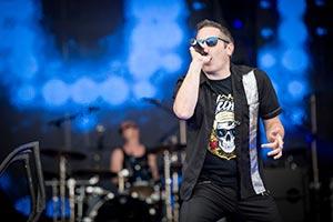 Sänger mit Schlagzeuger im Hintergrund. Blaues Bühnenlicht
