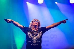 Sänger streckt beide Arme nach oben. Schönes blau weisses Bühnenlicht