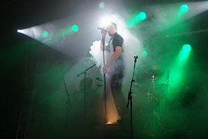Sänger steht auf einer Box im grühnen Nebel-Bühnenlicht