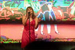 Sängerin im rotem, kurzem Kleid vor einer LED Leinwand während einer Betriebsfeier