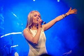 Sängerin im weissem Kleid steht im blauem Bühnenlicht