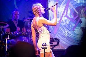 Sängerin im kurzem, weissem Kleid steht seitlich zum Publikum während einer Betriebsfeier in Niedersachsen