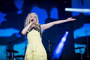Sängerin in einem gelbem Kleid auf einer großen Bühne während einer Firmenfeier