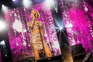 Sängerin in einem goldenen Glitzerkleid auf einer Firmenfeier.