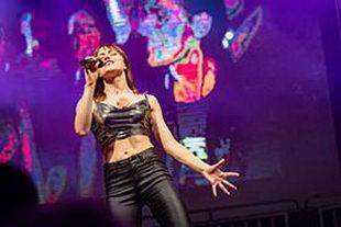Sängerin in coolem Lederoutfit vor großer LED Leinwand