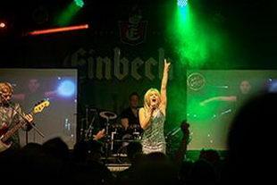 Sängerin hebt Arm und feuert das Publikum an