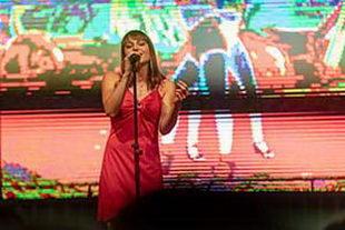 Sängerin im rotem Kleid mit einer Leinwand im Hintergrund