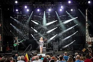 Sängerin im silbernem Kleid auf grosser Bühne. NDR Sommertour