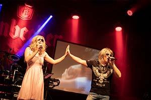 Sänger und Sängerin Hand in Hand im rotem Scheinwerferlicht