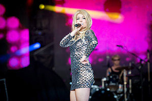 Sängerin im silbernen Kleid steht seitlich zum Publikum