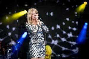 Sängerin auf einer großen Bühne im silbernem Glitzerkleid