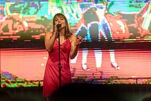 Sängerin im rotem Kleid vor einer LED-Leinwand