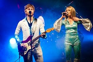 Bassist und Sängerin vorne an der Bühne. Blaues Bühnenlicht