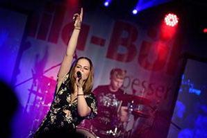 Sängerin im schickem, scharzem Kleid. Schlagzeuger im Hintergrund