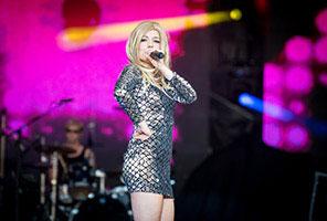 Sängerin im schickem, silbernem Kleid auf Bühne während einer Weihnachtsfeier