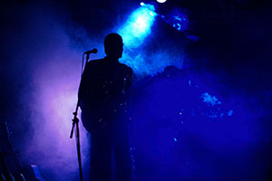 Bassist in wildem blauem Nebellicht bei einem Stadtfest in Schleswig Holstein