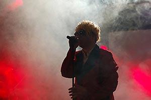 Sänger mit goldener Heino-Perrücke im Nebellicht