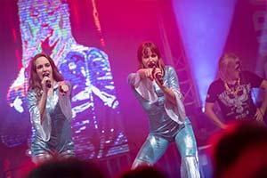 Beide Sängerinnen als ABBA verkleidet vor großer LED Leinwand