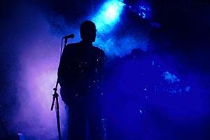 Bassist steht im dunkelblauem Bühen-Nebellicht